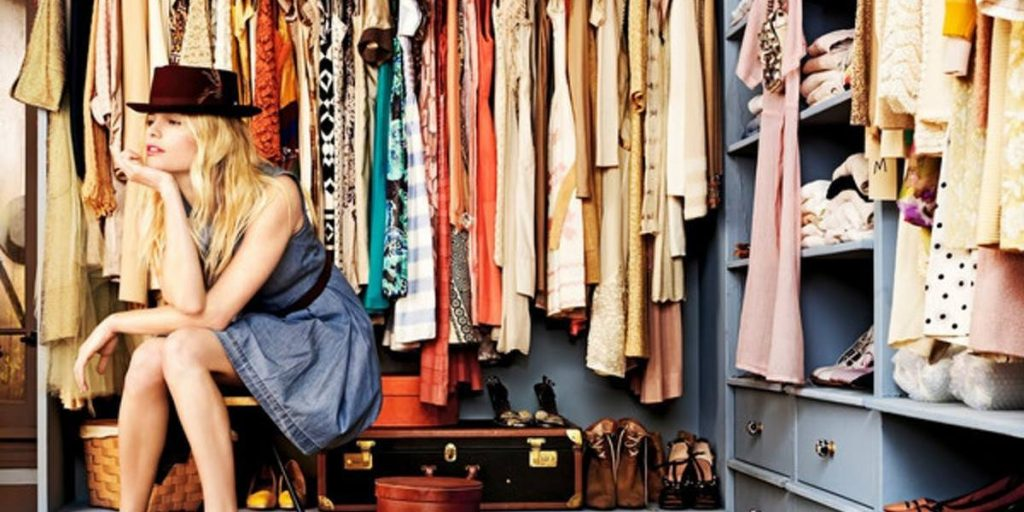 Girl sitting in her wardrobe thinking about what to wear